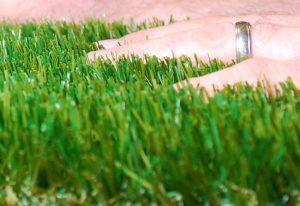 hand moving through artificial grass blades
