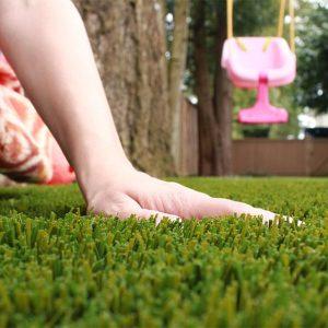 childs hand touching artficial grass
