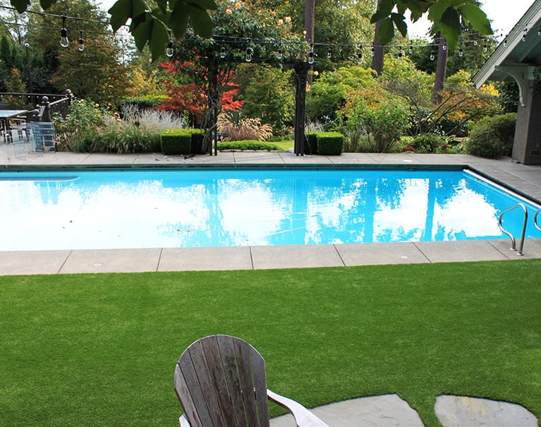artificial grass installed in backyard beside pool