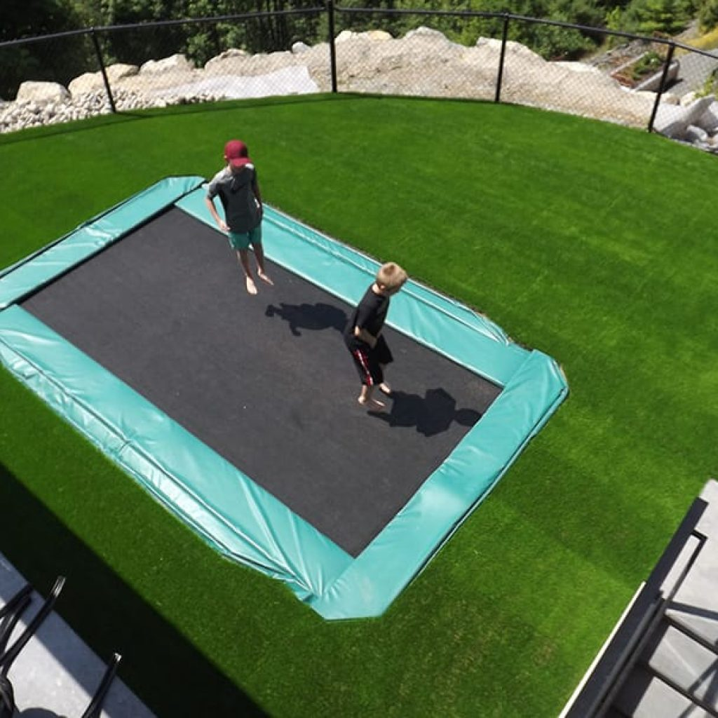 trampoline submerged in artificial grass backyard at home