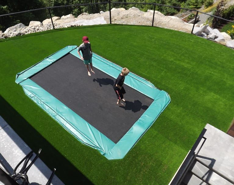 children playing on trampoline submerged within artificial grass lawn backyard