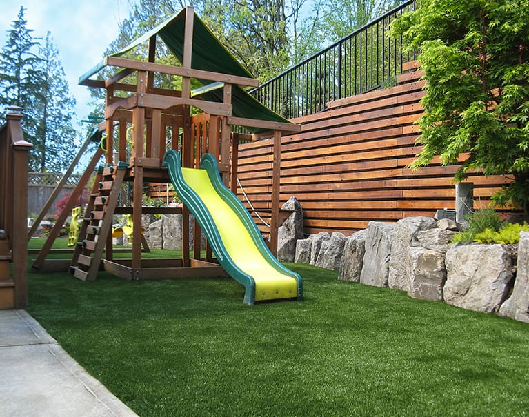 wooden playground structure with slide atop artificial grass lawn