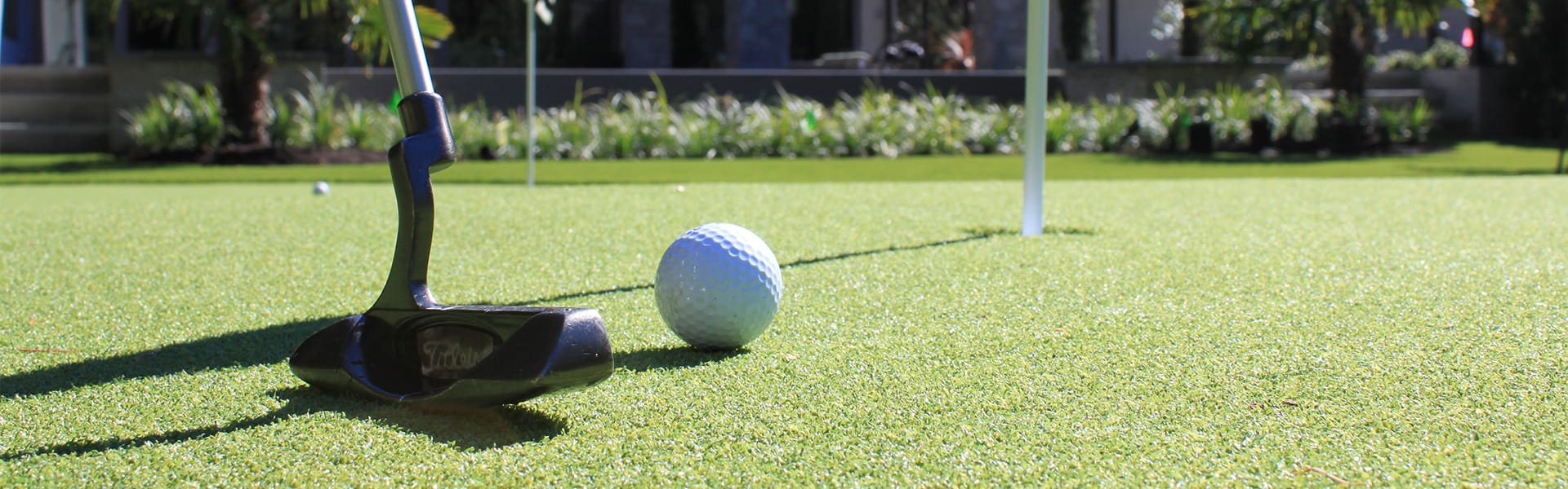 putting on artificial putting green grass in residential backyard