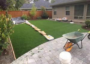 artificial grass installation in residential home backyard