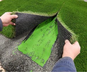 seaming together two pieces of artificial grass