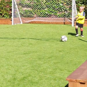 child playing soccer on artificial grass sports field