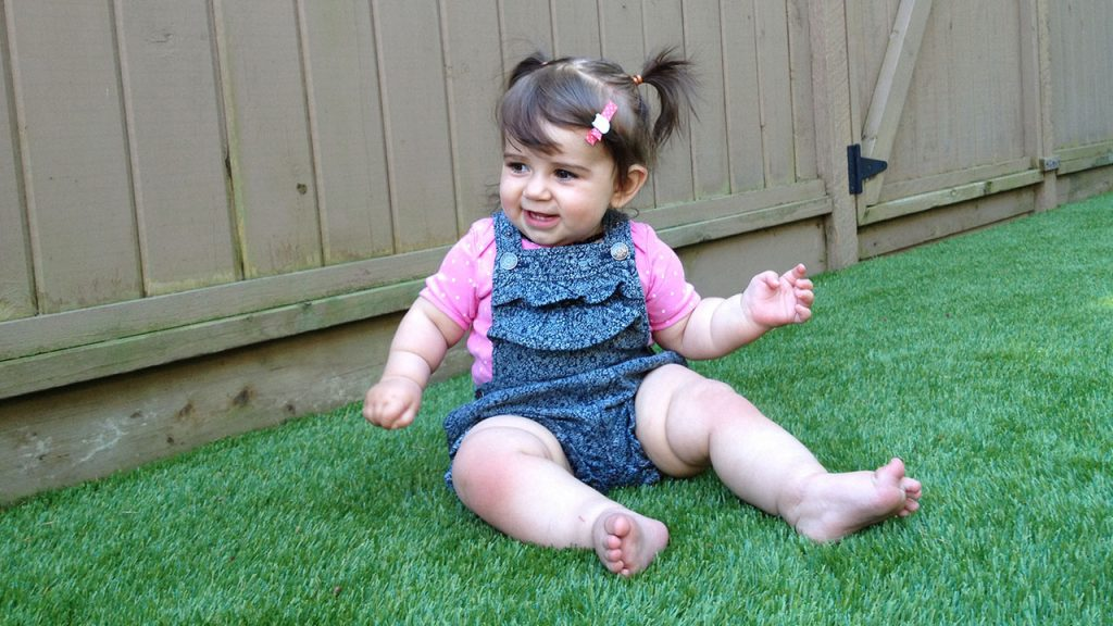 child sitting on artificial grass in backyard