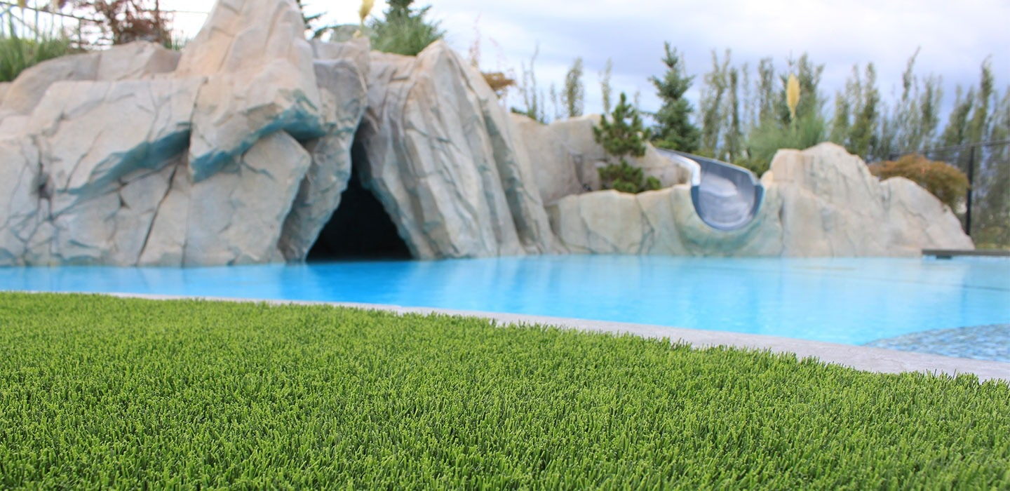 artificial grass lawn against pool side with slide in residential backyard