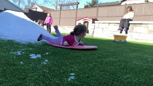 kids playing in snow covered artificial grass in canada winter